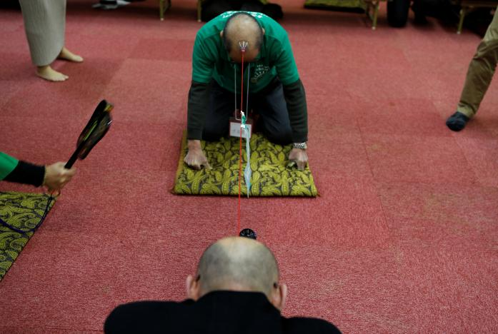Members of the Bald Men Club, take part in a unique game of tug-of-war by attaching suction pads onto their heads, at a hot spring facility in Tsuruta town