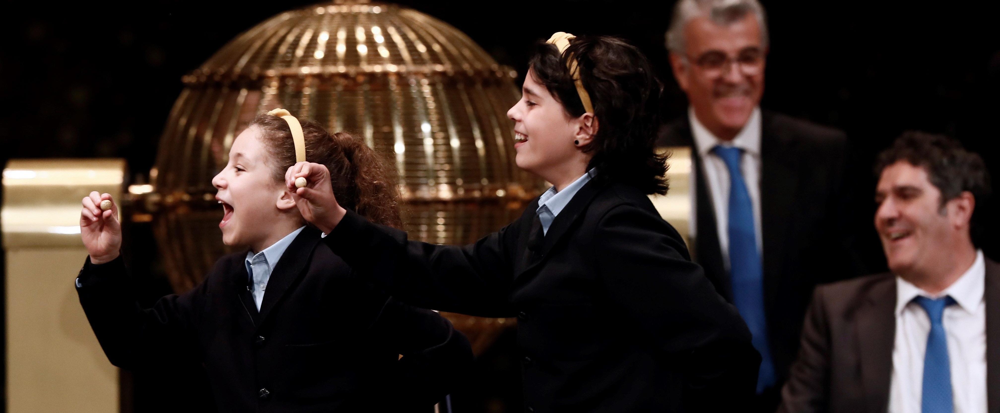 GRAF1277. MADRID, 22/12/2018.- Las niñas de San Ildefonso Aya Ben Hamdouch y Carla García Villnueva muestran el número 03.347 que ha sido agraciado con el primer premio, el Gordo, dotados con 400.000 euros al décimo, en el Sorteo de la Lotería de Navidad que se celebra hoy en el Teatro Real de Madrid. EFE/Mariscal