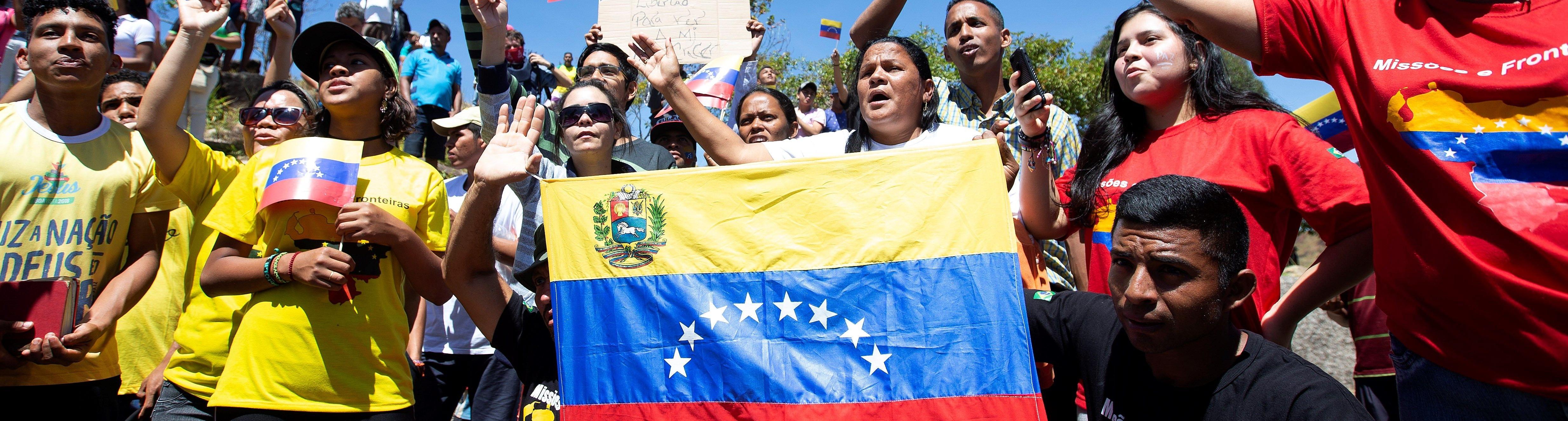 AME7796. PACARAIMA (BRASIL), 23/02/2019.- Personas celebran este sábado la llegada de la primera de las dos grandes camionetas cargadas con parte de la ayuda humanitaria de Brasil para Venezuela a la localidad Pacaraima, en el límite fronterizo entre ambos países, cerrado desde el jueves por orden del Gobierno de Nicolás Maduro. EFE/Joédson Alves