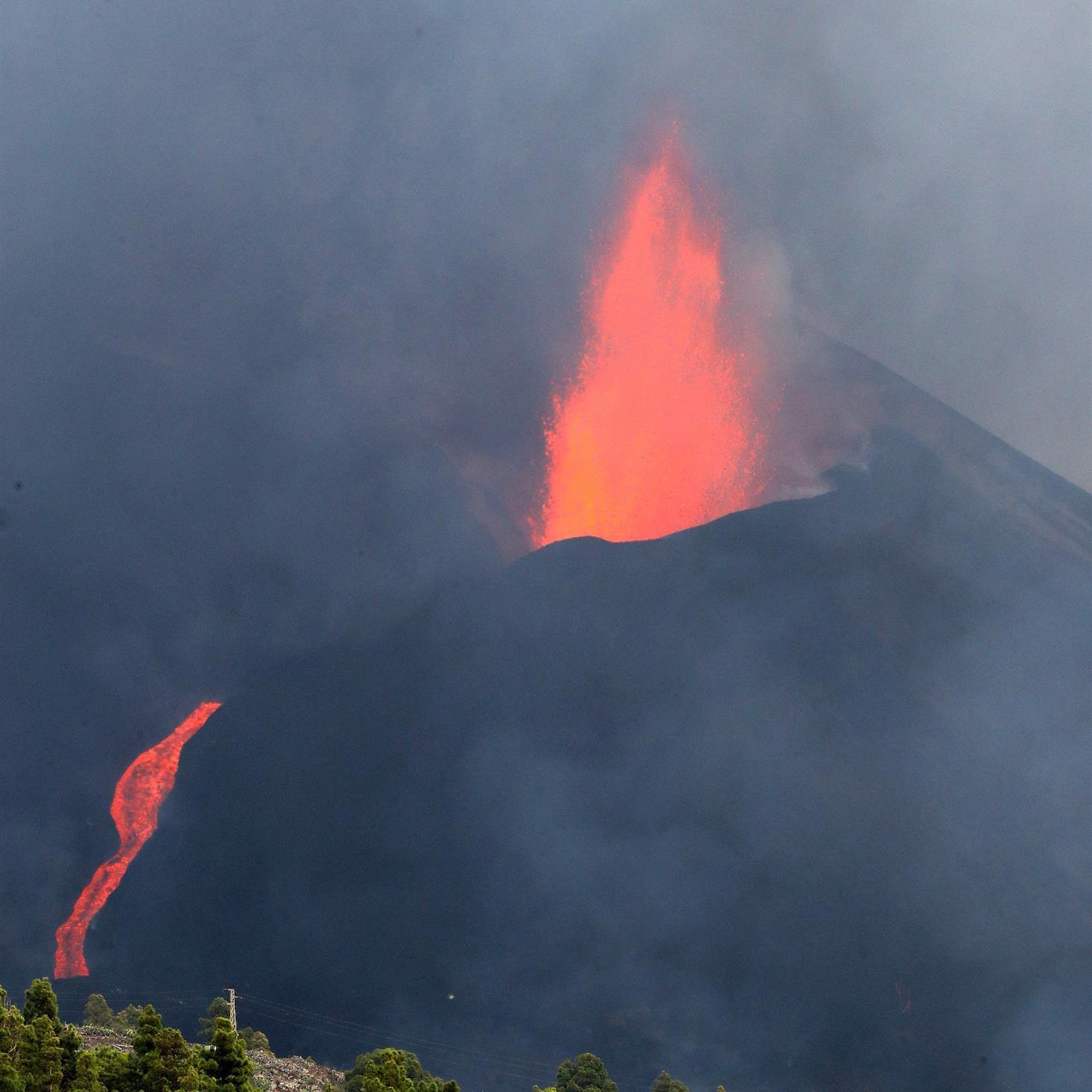 Erupción del volcán de La Palma y descenso de una colada de lava por la montaña.